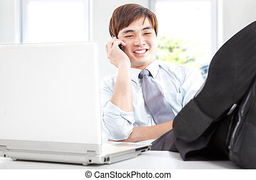 happy businessman taking a phone call in office