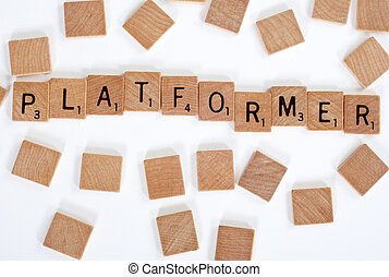 Scrabble tiles spell out 'Platformer' - Wood Scrabble tiles...