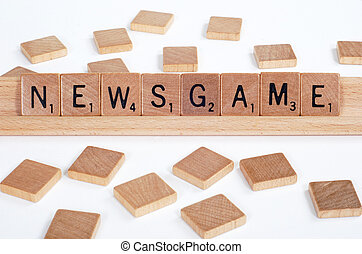 Scrabble tiles spell out Newsgame - Wood Scrabble tiles...
