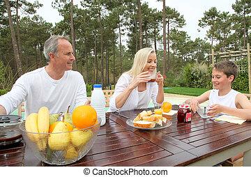 Family having breakfast in house garden