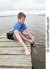 Kid sitting on a pontoon with fishing rod