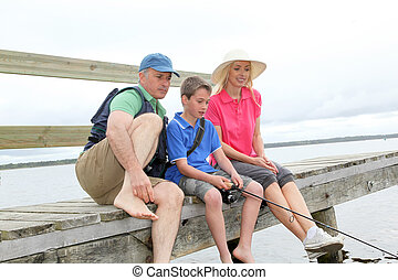 Family sitting on a pontoon with kid fishing