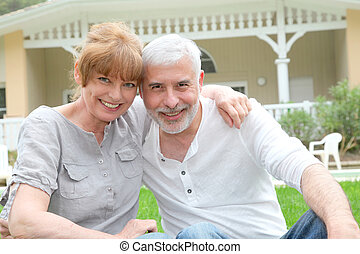 Portrait of senior couple standing in front of their home