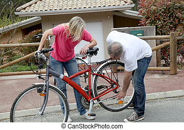 Couple checking bicycle before going on a ride