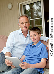 Father and son sitting in sofa with electronic tablet