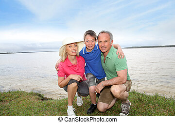 Portrait of happy family kneeling by a lake