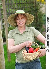 Senior woman standing in kitchen garden