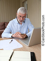 Senior man using calculator