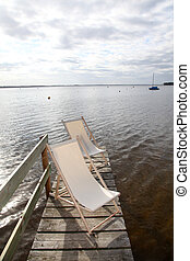 View of deck chairs set on a lake pontoon