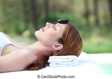 Woman laying on massage bed with hot stone on forehead