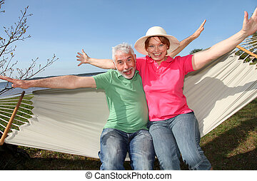 Happy senior couple sitting in hammock