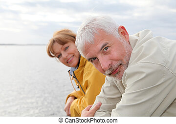 Portrait of senior couple standing by a lake