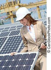Woman engineer checking solar panels setup