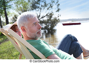 Senior couple resting in deck chair
