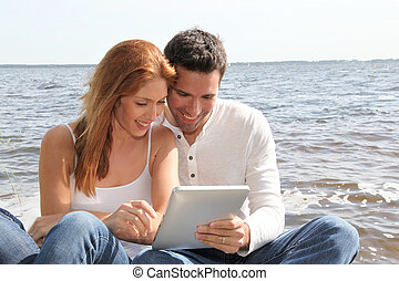 Couple using electronic tablet by a lake