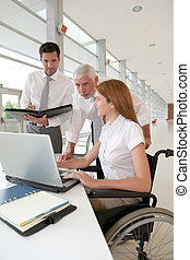 Handicapped woman attending a meeting in office