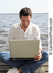 Man sitting on a pontoon with laptop computer