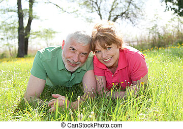 Portrait of senior couple laying in grass