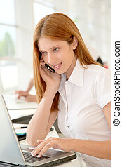 Smiling office worker in front of computer