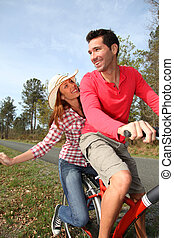 Couple riding bicycles in countryside