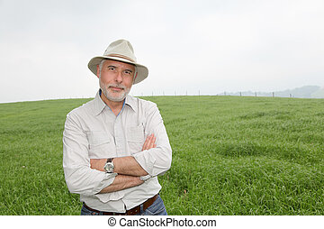 Senior man with hat in farmland