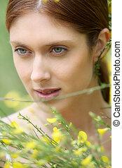 Portrait of beautiful woman in field of flowers