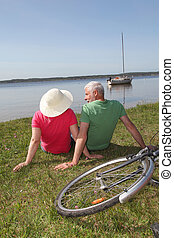 Senior couple riding bicycle in summer