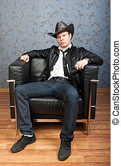 A stylish man sitting in leather chair in Interiors - Brutal...