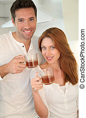 Couple in home kitchen drinking tea
