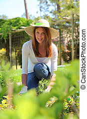 Beautiful woman planting flowers in garden