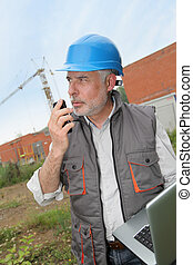 Construction manager on building site with laptop computer