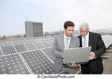 Business people standing by solar panels