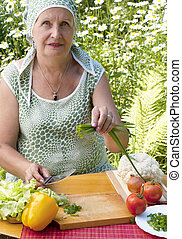 The adult woman cuts salad from fresh appetizing vegetables