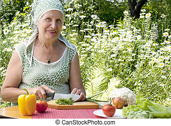 The adult woman cuts salad - The adult woman with a smile...