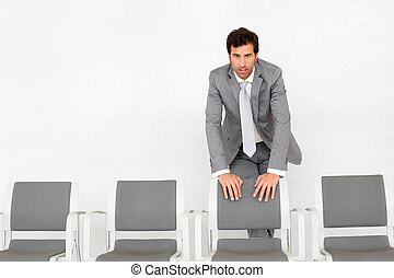 Man standing by chairs in waiting room