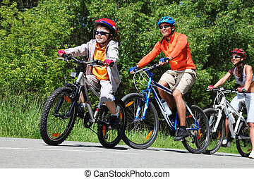 Summer speeders - Dynamic image of a family cycling in the...