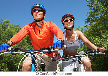 Cycling couple - Young smiling couple cycling through summer...