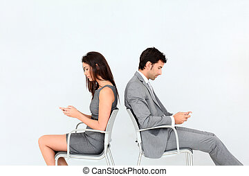 Business people sitting in chairs with mobile phone