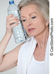Portrait of senior woman with bottle of water after...