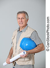 Closeup of senior engineer holding security helmet and plan