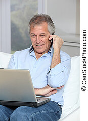 Senior man in sofa with laptop computer and mobile phone