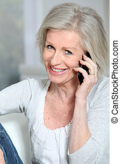 Happy senior woman talking on mobile phone