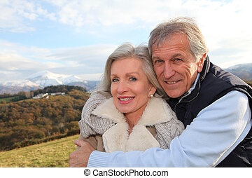 Portrait of happy senior couple in countryside