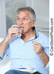 Senior man taking medicine