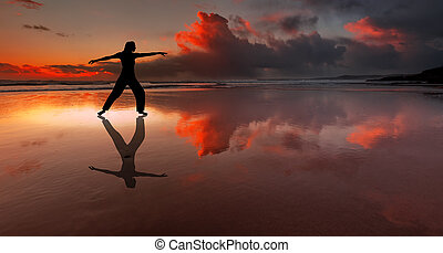 Silhouette of fitness person on a beach at sunset -...