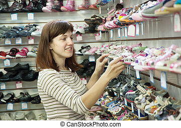 woman chooses baby shoes