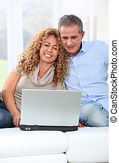 Couple surfing on internet at home