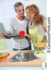 Couple cooking in kitchen with laptop computer