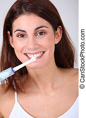 Young woman brushing her teeth with electric toothbrush