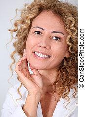 Portrait of beautiful woman looking at wrinkles in mirror
